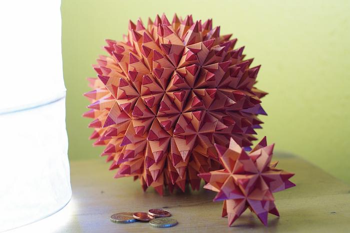 eine lampe und ein tisch aus holz, eine große pinke origami kugel aus papier und ein pinker bascetta stern mit pinken strahlen aus holz
