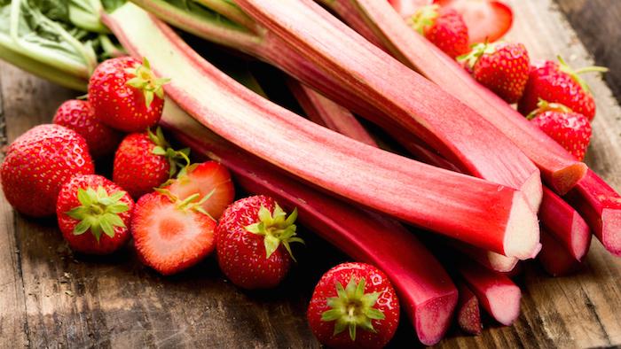 rhabarber roh essen, ein tisch aus holz und mit vielen langen roten geschnittenen rhabarber pflanzen mit grünen blättern, wie lange kann man rhabarber ernten, viele kleine rote erdbeeren mit kleinen grünen blättern
