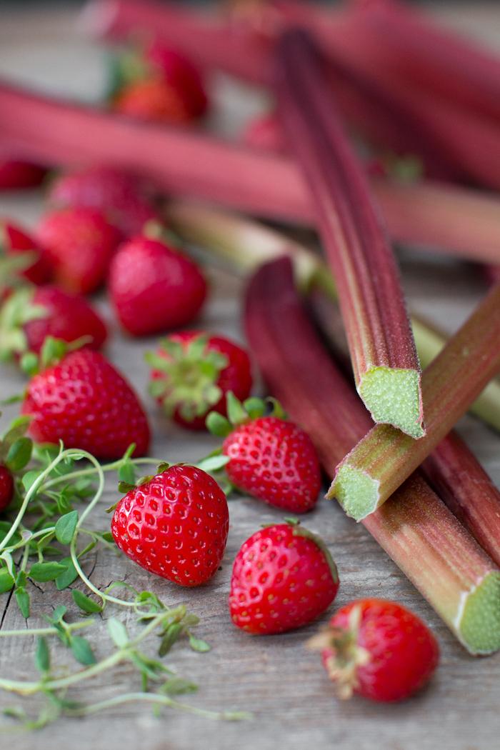 wie lange kann man rhabarber ernten, ein tisch aus holz und mit vielen langen geschnittenen rhabarber pflanzen, rhabarber zubereiten, viele kleine rote erdbeere mit grünen blättern, rhabarber rezepte