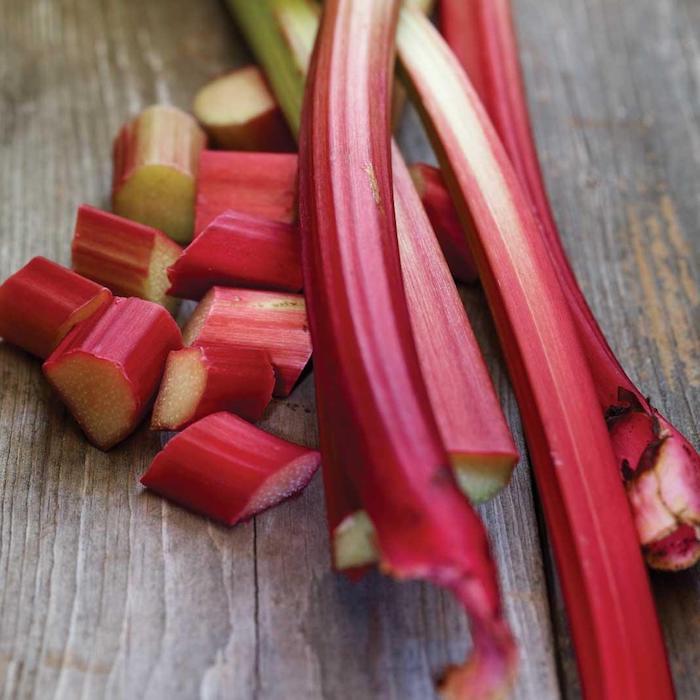 viele kleine geschnittene und lange rhabarber pflanzen, rhabarber erntzeit, ein tisch aus holz, wie lange kann man rhabarber ernten