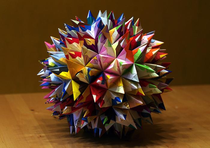 eine große bunte origami kugel aus papier und ein brauner tisch aus holz, eine kugel mit vielen kleinen roten, gelben, blauen, grünen und pinken strahlen aus holz