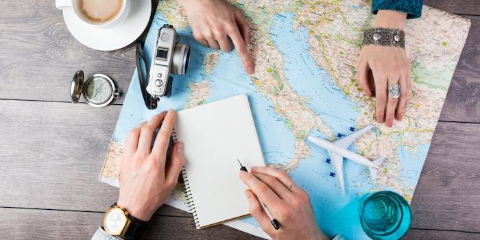 geld sparen und reisen, ein tisch aus holz und eine weltkarte, vier hände und bleistift