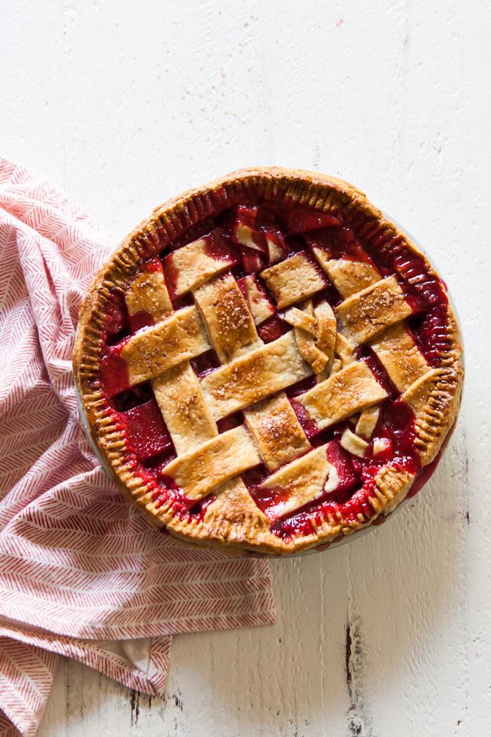 ein weißer tisch mit einer roten decke, ein teller mit einem roten erdbeer rhabarber kuchen mit einer roten erdbeer rhabarber marmelade, rezepte mit rhabarber
