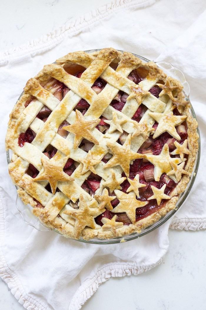 ein roter erdbeer rhabarber kuchen mit einer roten erdbeer rhabarber marmelade, ein tisch mit einer weißen decke
