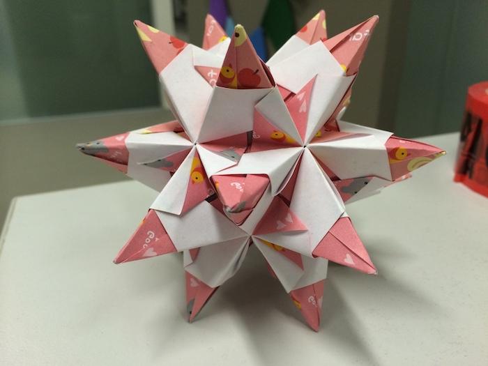 ein großer bascetta stern aus einem pinken papier mit kleinen gelben vögeln und mit kleinen pinken sternen und ein weißer tisch, basceta stern papier