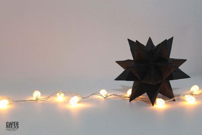 ein kleiner schwarzer bascetta stern mit vielen kleinen schwarzen strahlen aus papier und viele kleine leuchten, einen schwarzen bascetta stern basteln