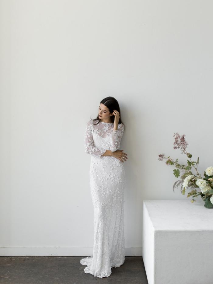 ein schneeweißes Kleid, mit Spitze gedeckt, Brautkleid Hippie, schwarzhaarige Braut