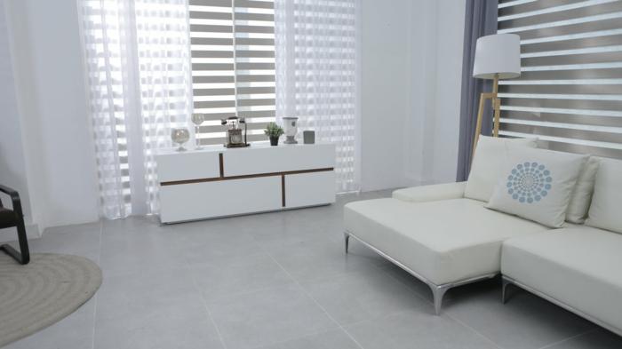 eine weiße Einrichtung, Dekoideen Wohnzimmer, graue Fliesen als Bodenbelag, runder Teppich