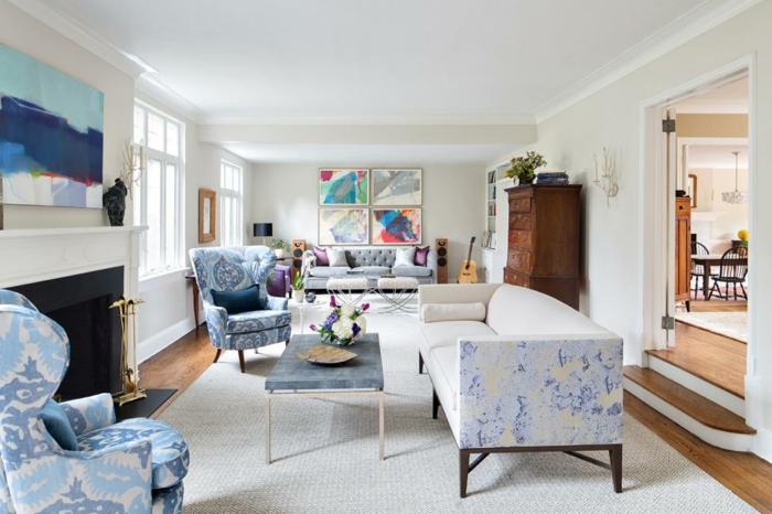 zwei blaue Sessel, ein Sofa mit kleinen blauen Motiven, ein weißer Teppich, ein kleiner Couchtisch, Dekoideen Wohnzimmer