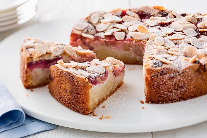 ein weißer tisch mit einem roten rhabarber blechkuchen mit einer roten erdbeer rhabarber marmelade, ein weißer tisch aus holz und eine kleine blaue decke, rhabarber zubereiten