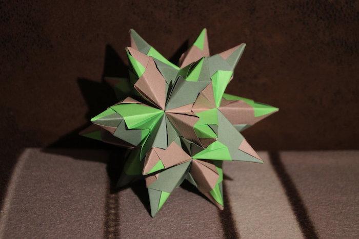 eine braune wand und eine braune decke, einen grünen origami stern falten, ein bascetta stern mit braunen und grünen strahlen aus papier