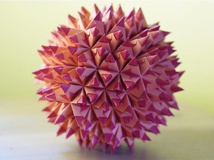 eine große pinke kugel mit vielen kleinen pinken und violetten strahlen aus papier, origami falten anleitung, basteln mit papier