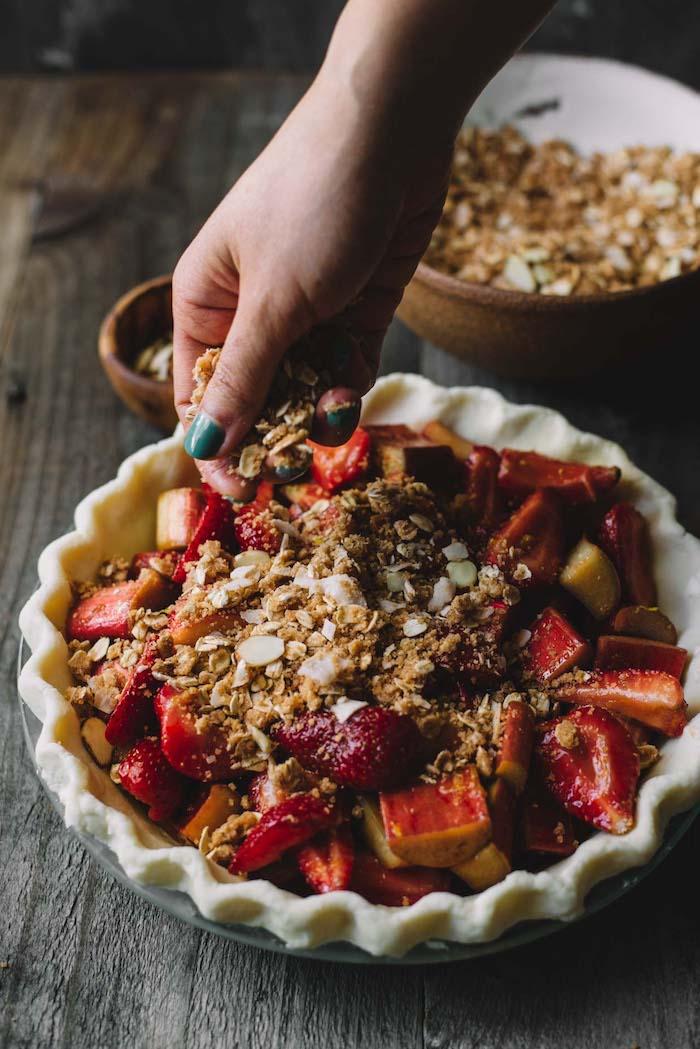 eine schüssel mit vielen kleinen roten geschnittenen erdbeeren und rhabarber pflanzen , eine hand mit einem grünen nagellack, rhabarber zubereiten