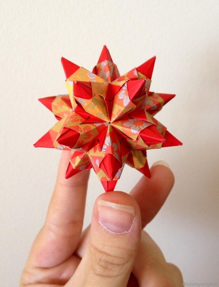 eine große hand und ein kleiner roter bascetta stern aus einem roten papier und mit vielen kleinen weißen blumen