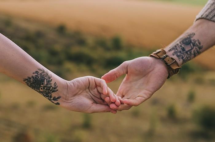 eine hand mit einem braunen armbanduhr und einer schwarzen tattoo am handgelenk. paar tattoo, eine hand mit tattoo mit vielen schwarzen blättern