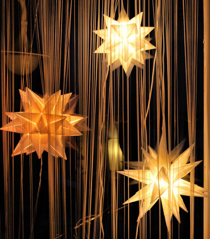 drei große gelbe bascetta sterne aus papier und mit gelben strahlen und leuchten, bascetta stern beleuchtet, ein fenster und eine lampe