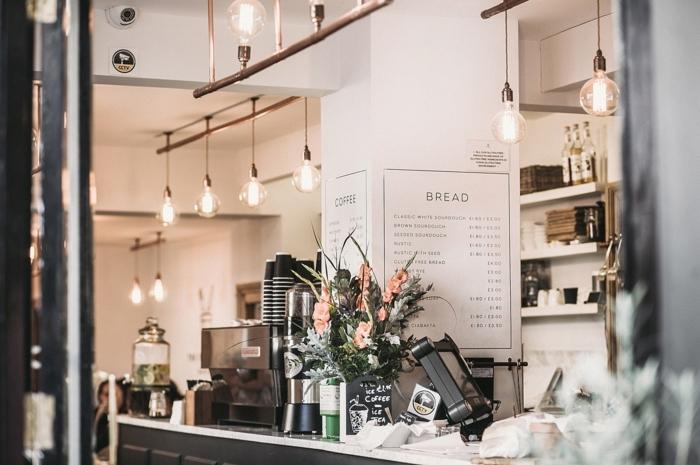 eine moderne Küche mit Theke, Wandfarbe Hellgrau, viele hängende Lampen
