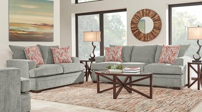 graue Sofas mit roten Kissen, ein runder Spiegel, zwei Lampen, moderne Wohnzimmer
