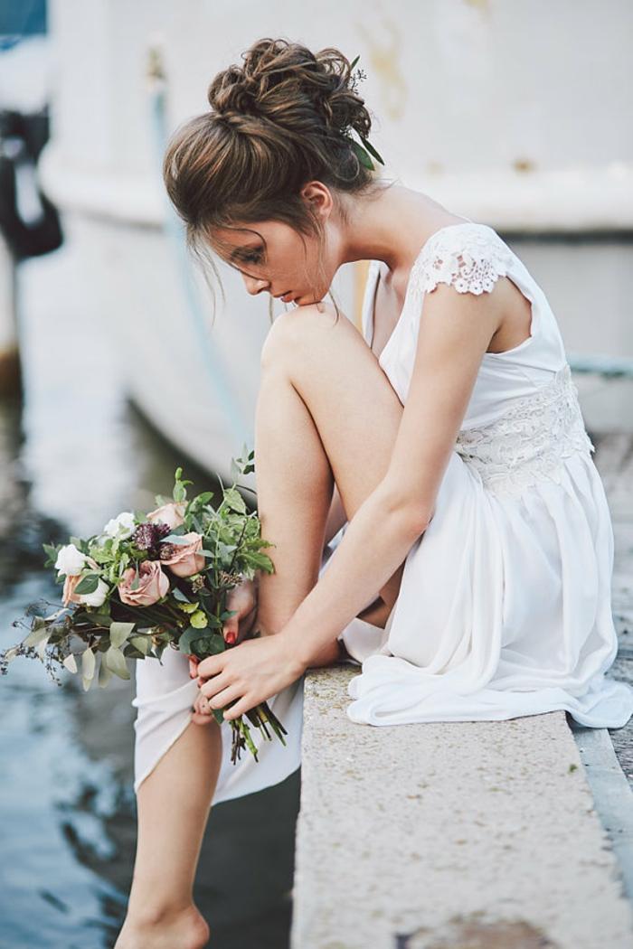 eine in Gedanke vertiefte Braut, lässige Boho Brautkleid, ein vintage Brautstrauß