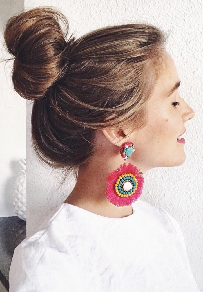 ein hübsches Mädchen mit bunten Ohrringen, Dutt Haare in lässiger Frisur
