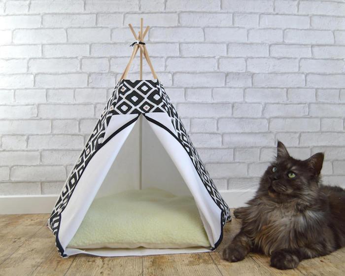 eine kleine schwarze katze mit grünen augen, ein boden aus holz, ein kleines weißes zelt aus einem weißen stoff und mit einem grünen kissen und mit langen stöcken aus holz, ein katzenzelt selber bauen, eine wand aus vielen weißen ziegeln