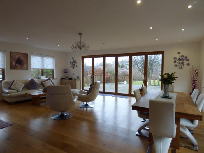 Laminatboden, Deckenleuchte, weißes Sofa und zwei Sessel, moderne Wandfarbe