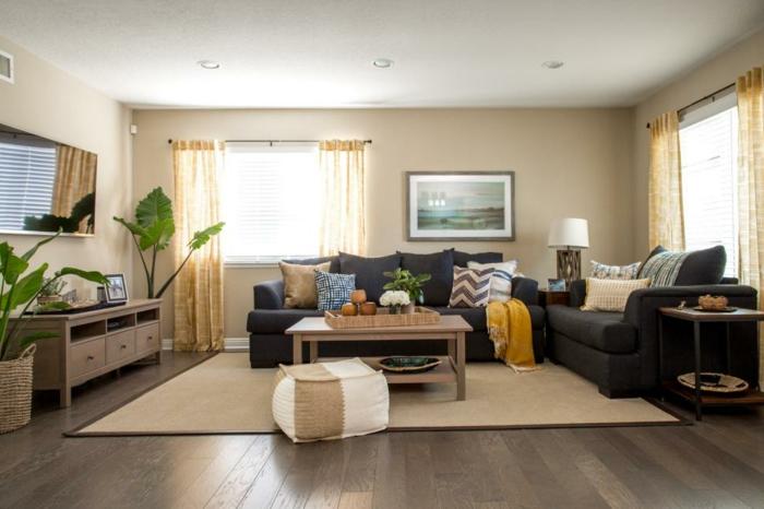 ein brauner Teppich, schwarze Sofas, ein herrliches Bild an der Wand, Dekoideen Wohnzimmer