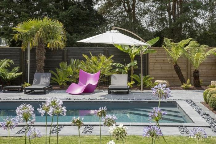 gartendeko, englischer stil, pool im garten mit drei liegestühlen, rosastuhl, schwarze dekorationen, sonnenschirm, blumen