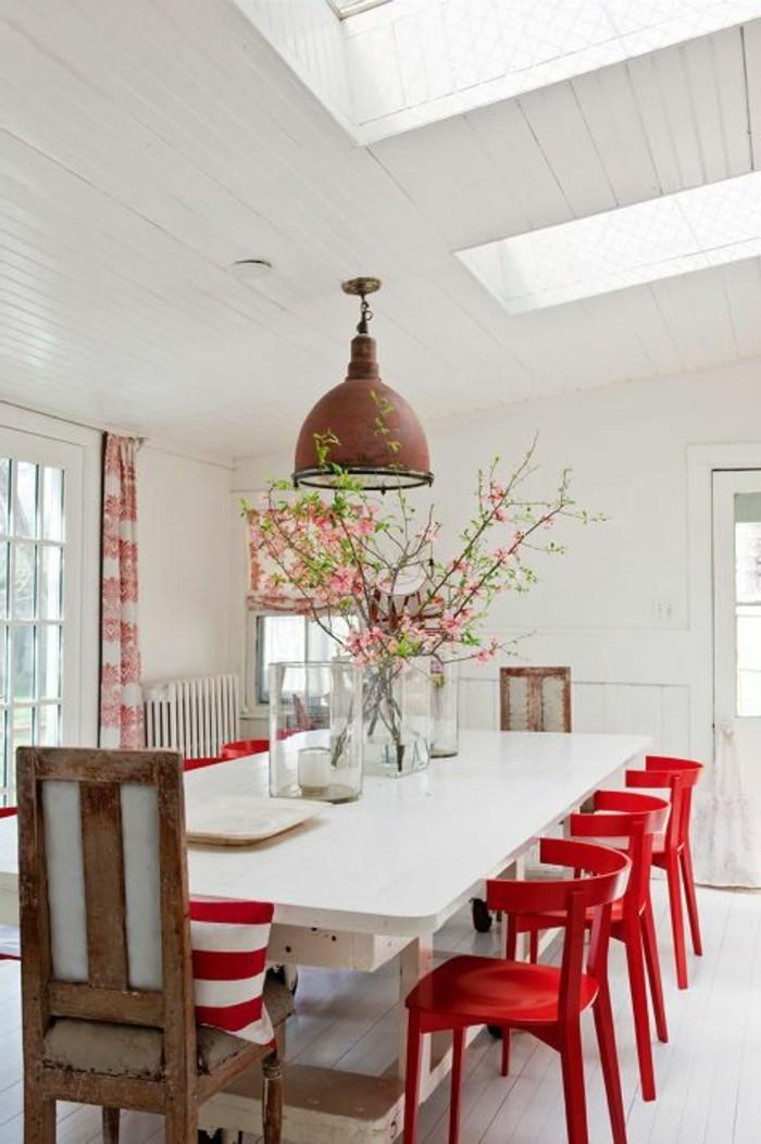 farbenfrohe esstisch deko auf weißem tisch, rote stühle und rote blumen in der vase