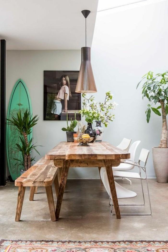 schöne esszimmer deko, robuster stil mit holztisch und grühe pflanzen vom garten in vase auf dem tisch, palme in topf am bodern, wanddeko, wandbild mit einer frau