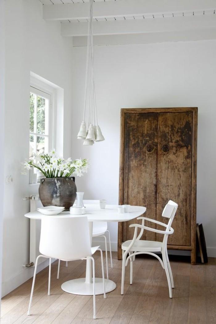 robustes esszimmer einrichten, ein großer alter schrank, ausgetragener effekt, weiße blumen in einer retro vase, kontrast mit den modernen möbeln
