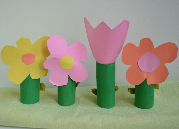 eine Wiese als Bastelideen mit Klopapierrollen für kleine Kinder, rosa Tulpe und andere Blumen