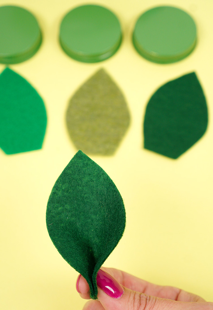 Blätter aus grünem Filzstoff ausschneiden, Obst Kerzen dekorieren