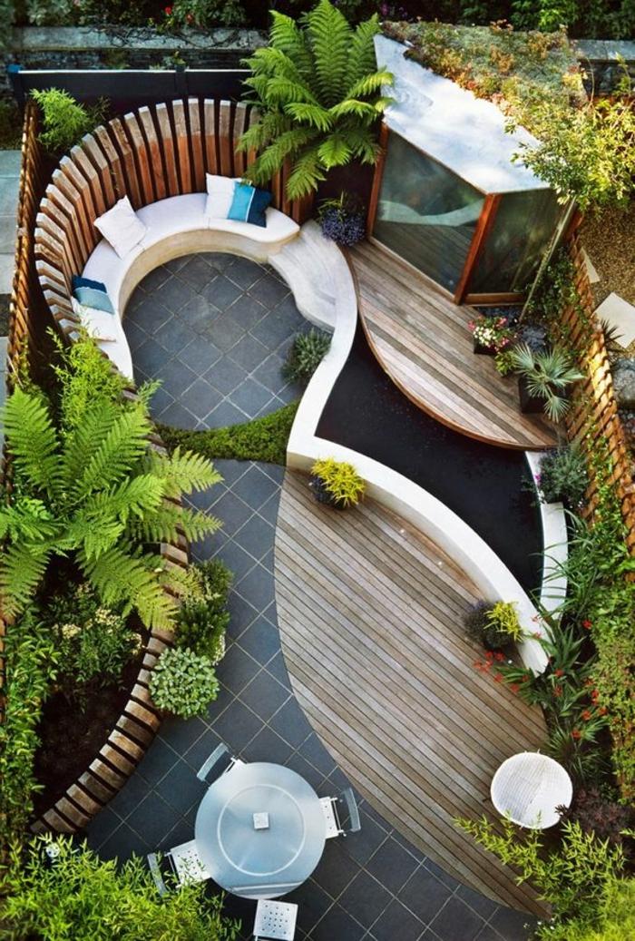 garten englischer stil, ein bild von oben gemacht, schöne sitzecke in runder form mit kissen dekoriert und palmen
