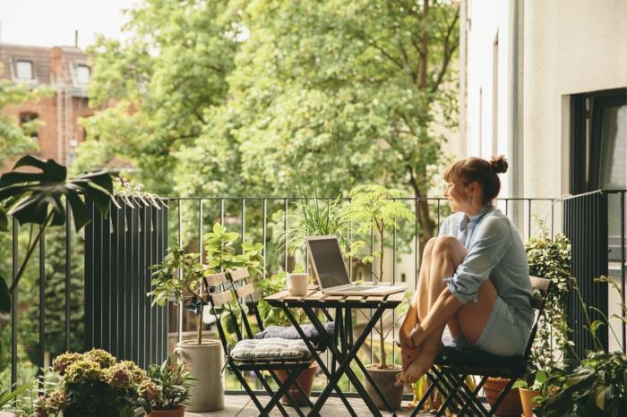 eine frau sitzt und lächelt, gemütlicher ort, gartenmöbel für kleinen balkon