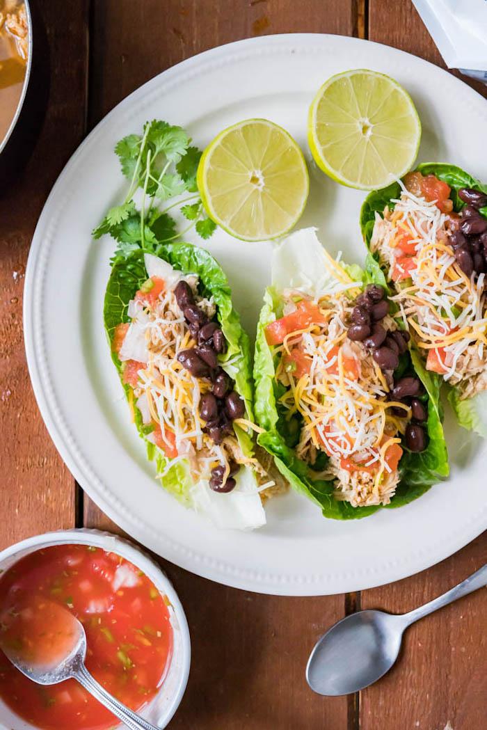 gesundes abendessen, tacos aus grünem salat gefüllt mit geschnittenen tomaten, bohnen und käse