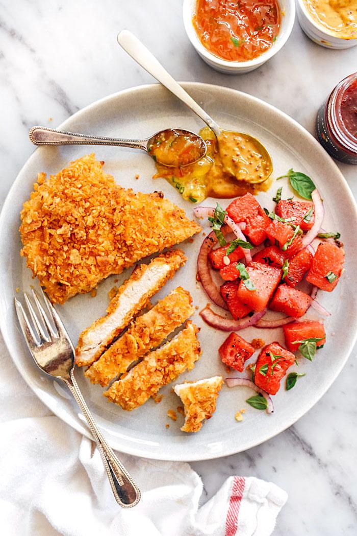 fleisch mit salat aus tomaten, gesundes abendessen warm, zwei löffel und eine gabel
