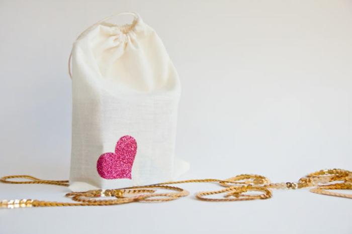 eine weiße Tüte, Geschenktüten basteln, rosa Herz als Verzierung in der Ecke