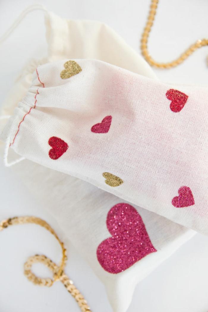 weiße Tüten mit rosa Herzen und goldene Stücke, Geschenktüten basteln