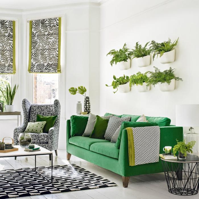 grünes Sofa, graue Dekorationen, ein vertikaler Garten, weiße Wände, Wohnzimmer Einrichtung