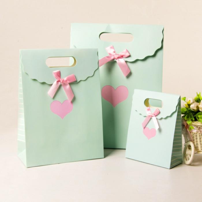 grüne Papiertüten, rosa Herzen in der Mitte, Geschenktüte falten mit rosa Schleifen