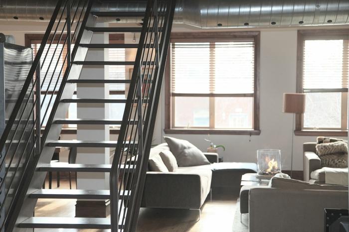 eine graue Einrichtung, weiße Wände, Rollos an den Fenstern, schöne Wohnzimmer