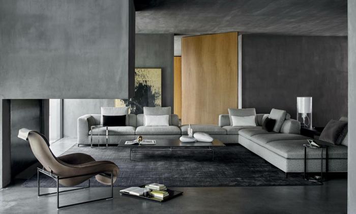 ein Zimmer in grauer Farbe, grauer Teppich, schwarze und weiße Kissen, Einrichtung Wohnzimmer
