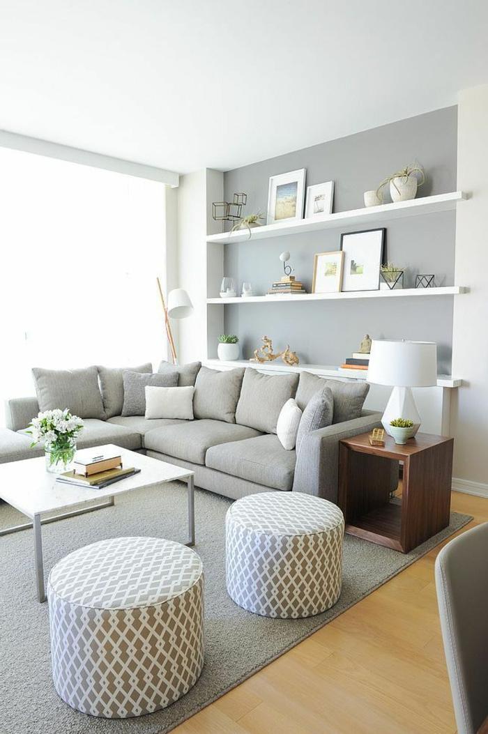 ein grauer Teppich, zwei bunte Hocker, ein kleiner Tisch, Regale voller Bilder