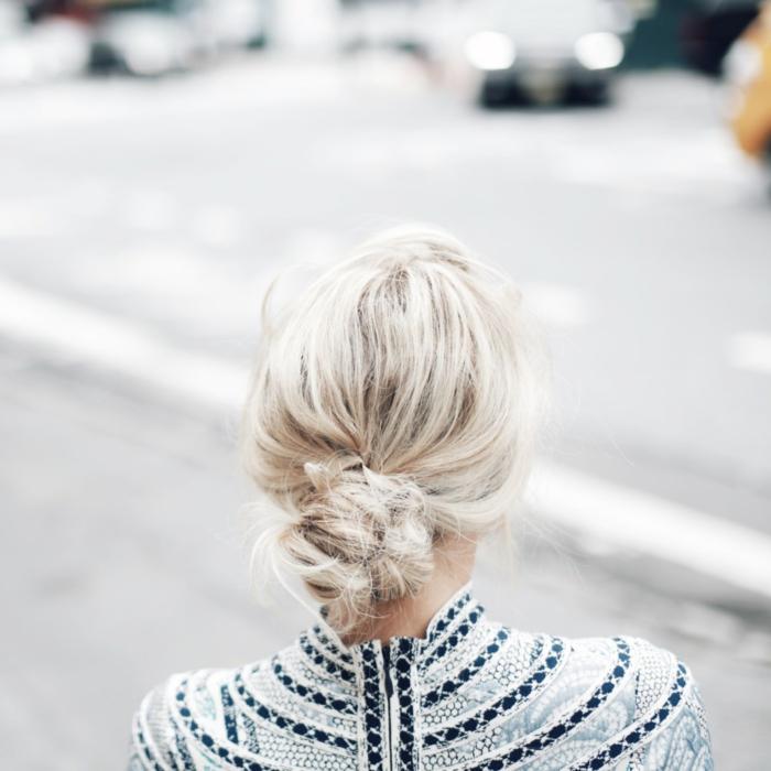 blonde Haare, ein Dutt wie Zopf, weiße Bluse mit schwarzen Streifen