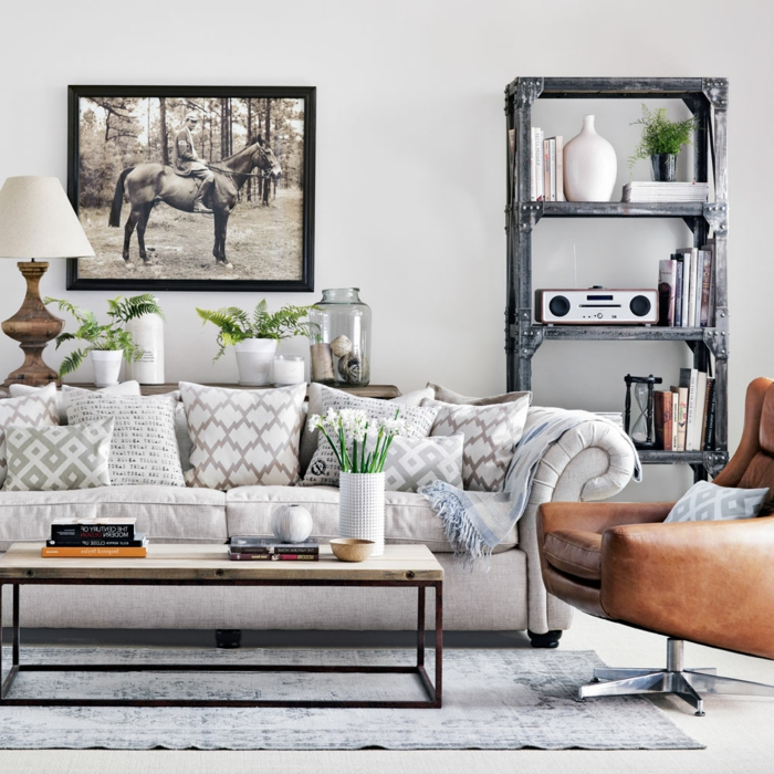 Wandfarbe Hellgrau, weißes Sofa, ein vintage Regal, oranger Sessel