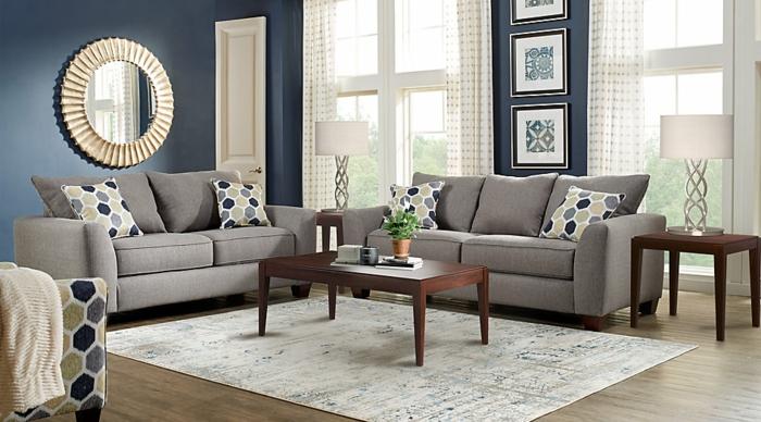 weißer Teppich, graue Sofas, ein Tisch aus Holz, runder Spiegel mit rundem Rahmen