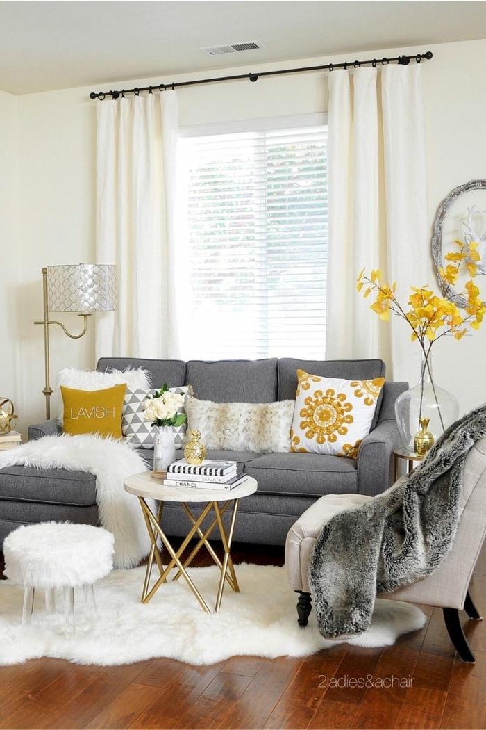 graues Sofa, gelbe Kissen, weißer Teppich, runder Tisch, Wohnzimmer Einrichtung