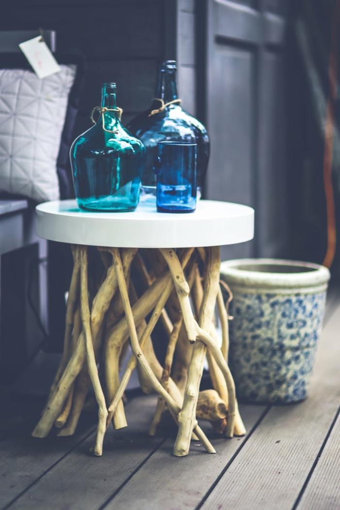 ein kleiner, runder Tisch, viele Flaschen, moderne Wandfarben, ein Blumentopf