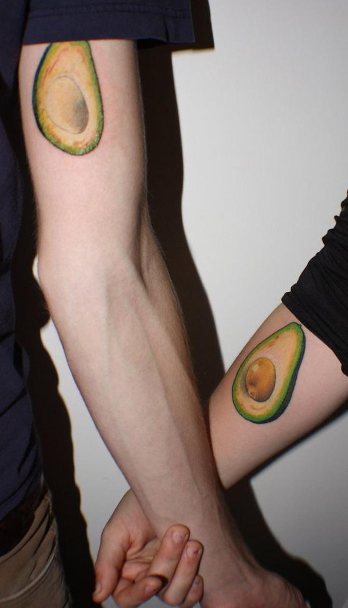 eine weiße wand und zwei hände mit einem grünen avocado tattoo, paar tattoo, zwei tattoos die sich ergänzen